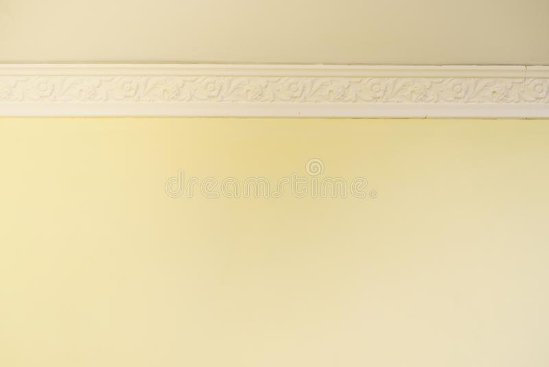 White cornce on wall. Decorative white cornice on yellow wall, home room decor, design and architecture concept royalty free stock photo