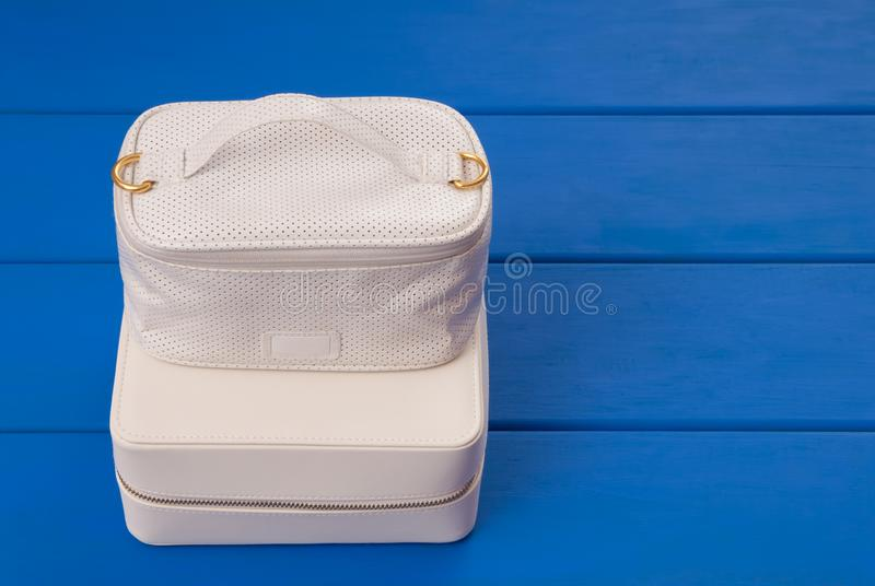 White cosmetic bags are on blue table, beauty products, make-up royalty free stock photos