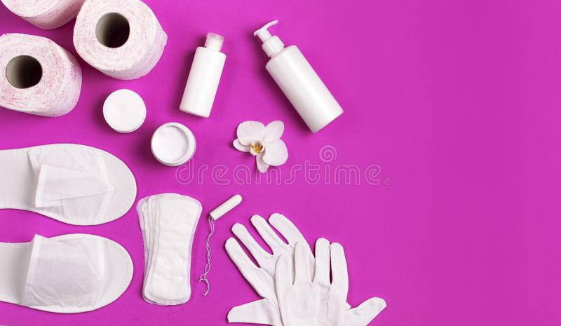 White cosmetic bottle containers gloves slippers hygiene items gasket tampon cotton pads toilet paper tablet orchid flower on pink. Background top view flat lay royalty free stock photos