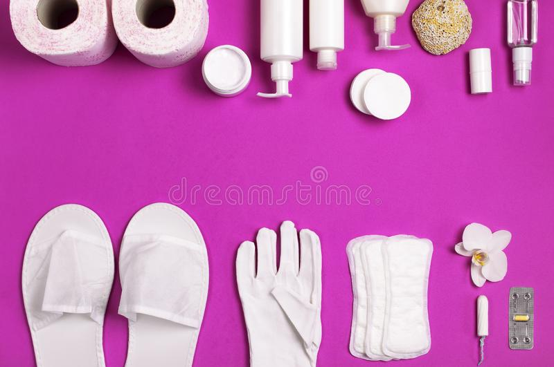 White cosmetic bottle containers gloves slippers hygiene items gasket tampon cotton pads toilet paper tablet orchid flower on pink. Background top view flat lay stock images