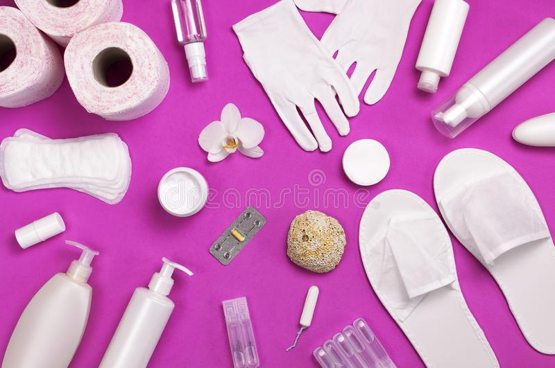 White cosmetic bottle containers gloves slippers hygiene items gasket tampon cotton pads toilet paper tablet orchid flower on pink. Background top view flat lay royalty free stock images