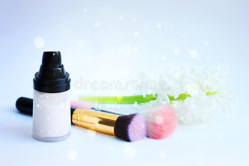 White cosmetic bottle containers, makeup brushes, white hyacinth flowers on pastel blue background. Cosmetics SPA branding mock-up royalty free stock images