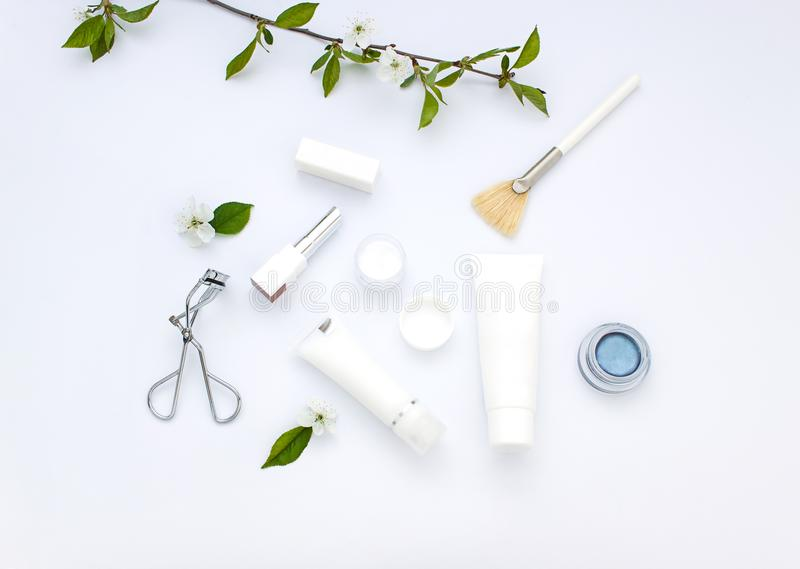 White cosmetics flat lay with flowers and leaves. Clean beauty concept. White organic cosmetics flat lay with flowers and leaves. Clean beauty concept stock photo