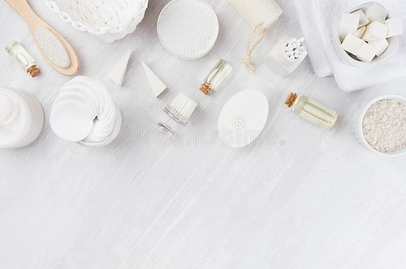 White cosmetics set of natural products for body care and bath accessories as border on white wood board, top view. White cosmetics set of natural products for royalty free stock photo