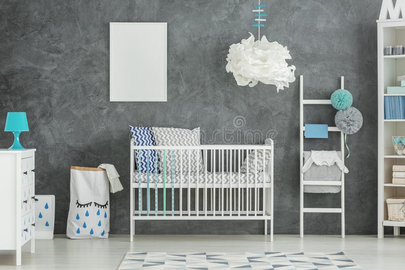 White cot in a room. With grey wall and a mint lamp stock images