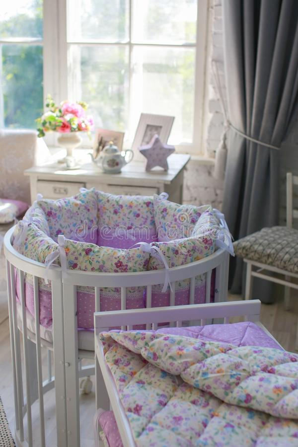 White Cribs for babies, round shape. White cots, round shape, in the interior, bright interior, purple linens, accessories in the Provencal style, white vintage stock photo