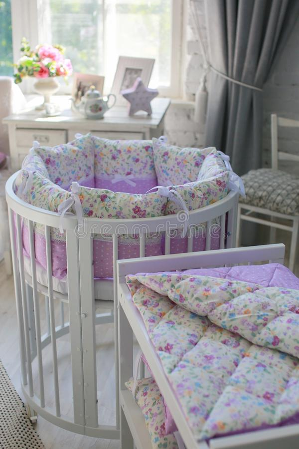 White Cribs for babies, round shape. White cots, round shape, in the interior, bright interior, purple linens, accessories in the Provencal style, white vintage stock images