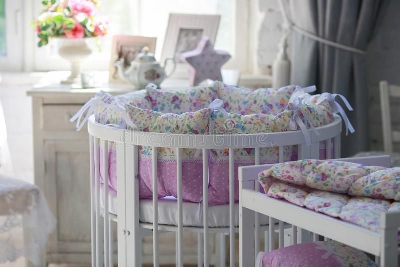 White Cribs for babies, round shape. White cots, round shape, in the interior, bright interior, purple linens, accessories in the Provencal style, white vintage stock photography