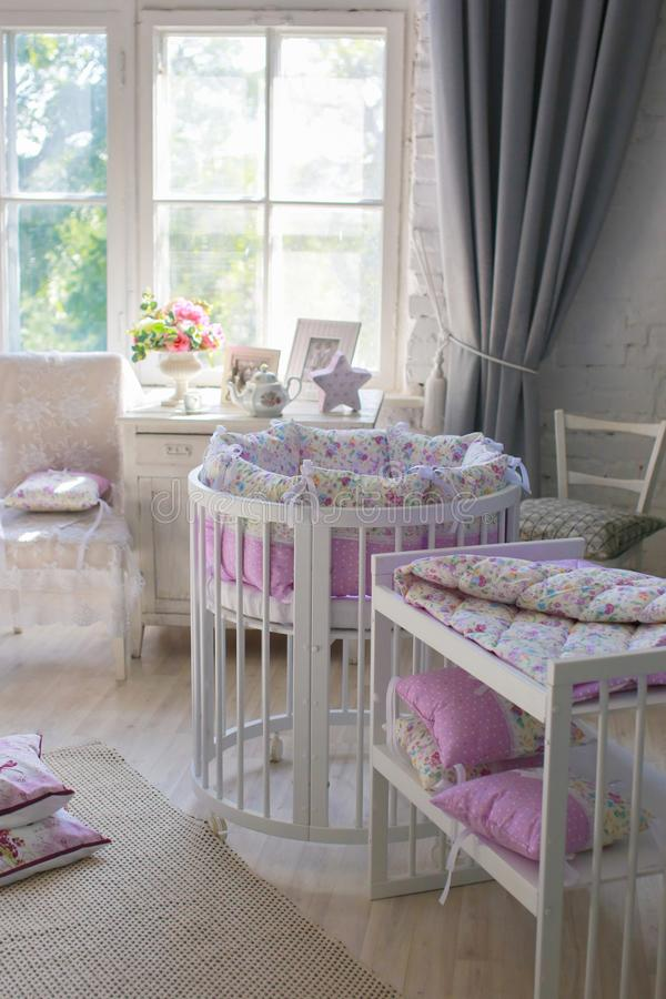 White Cribs for babies, round shape. White cots, round shape, in the interior, bright interior, purple linens, accessories in the Provencal style, white vintage stock image