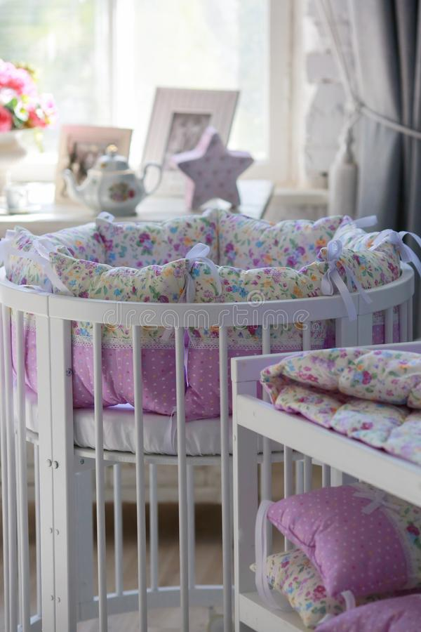 White Cribs for babies, round shape. White cots, round shape, in the interior, bright interior, purple linens, accessories in the Provencal style, white vintage royalty free stock photos