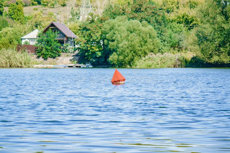 White cottage house on the other side of the river. Sunny day. A red buoy floats on the water royalty free stock photos