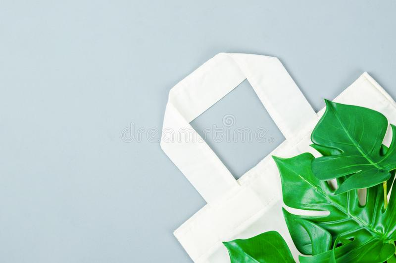 White cotton bag and green leaves royalty free stock photos