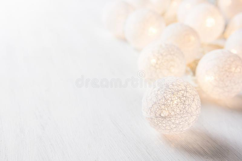 White Cotton Ball Garland with Sparkling Lights on Wood Table. Soft Pastel Colors. Christmas New Year Ornament Decoration. royalty free stock image