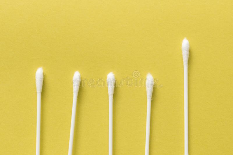 White cotton bud or cotton swab over on yellow background royalty free stock image
