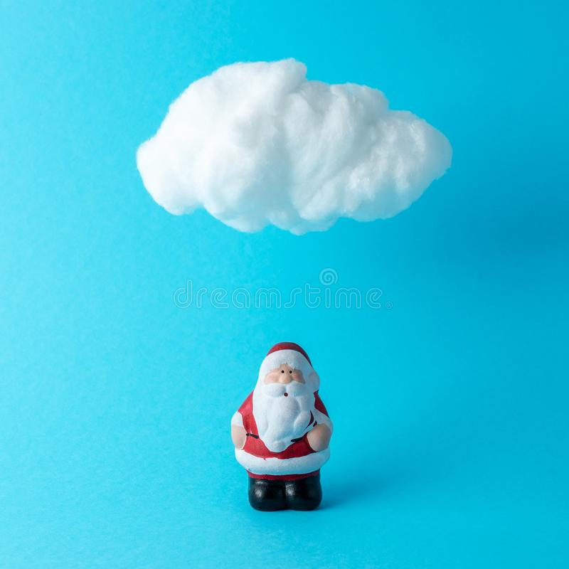 White cotton cloud with small Santa Claus against pastel blue background. Minimal Christmas or New Year concept stock image