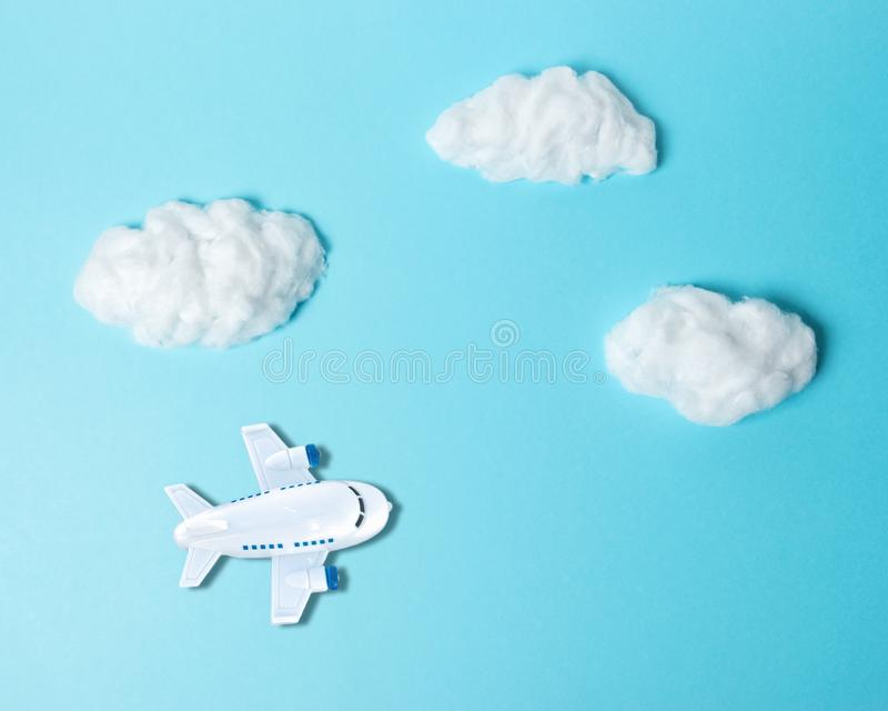 White cotton clouds with small airplane on pastel blue background. Minimal concept royalty free stock image