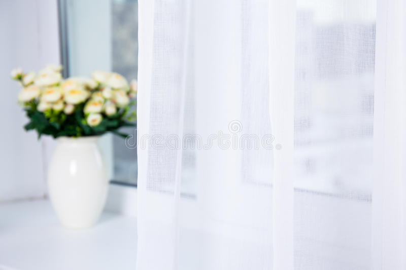 White cotton curtain and flowers on the window royalty free stock photography