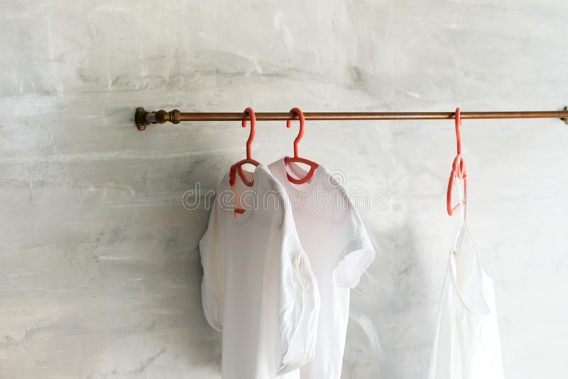 White cotton t-shirts and dresses plastic hangers. White cotton t-shirts and dresses on plastic hangers hangs on metal bar in hi-tech style room. Open wardrobe stock photography