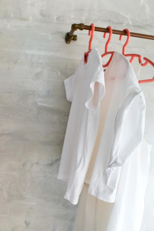 White cotton t-shirts and dresses plastic hangers. White cotton t-shirts and dresses on plastic hangers hangs on metal bar in hi-tech style room. Open wardrobe stock photo