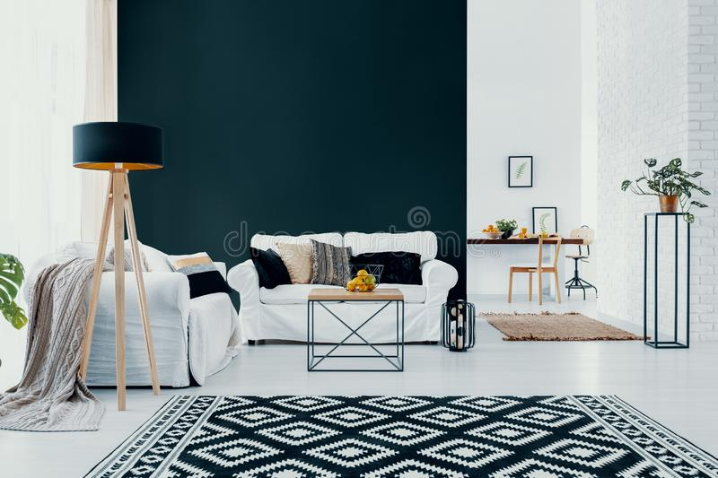 White couch against black wall in modern living room interior with patterned carpet. Real photo royalty free stock images
