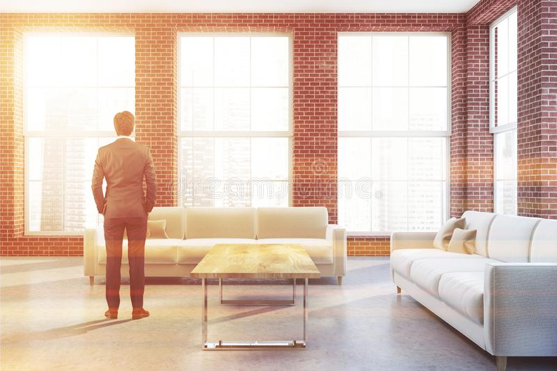 White couches in brick living room, businessman stock photo