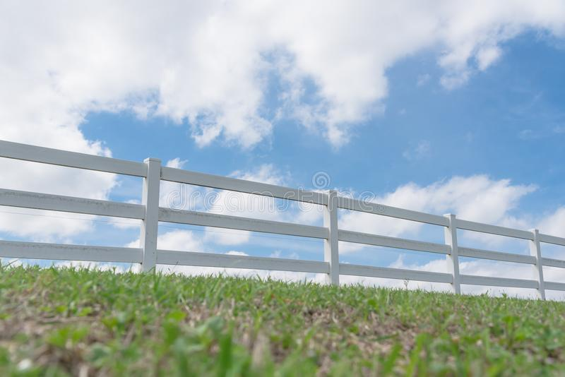 Country style wooden fence against cloud blue sky. White country style wooden fence against cloud blue sky. White fences on green grass at farm ranch land field royalty free stock photography