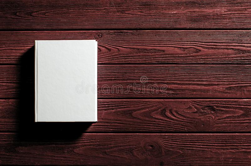 The white-cover book is on a textured wooden table. Copy spase, education, library, background, paper, empty, design, old, open, page, classic, retro, vintage stock photography