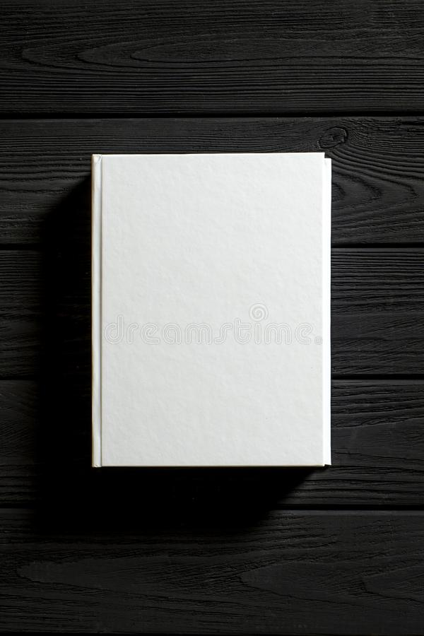 The white-cover book is on a textured wooden table. Copy spase, education, library, background, paper, empty, design, old, open, page, classic, retro, vintage stock photo
