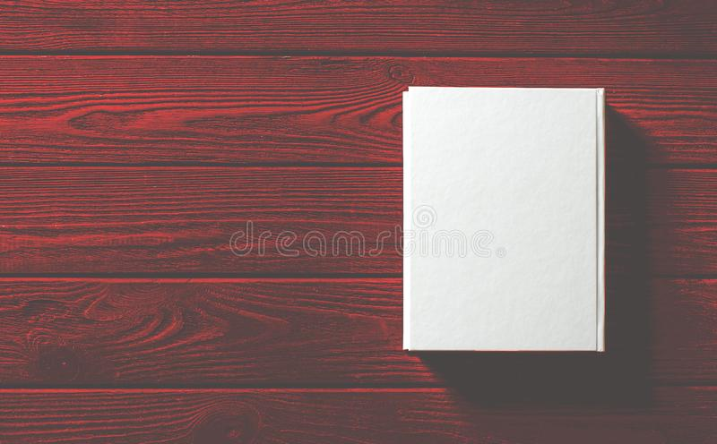 The white-cover book is on a textured wooden table. Copy spase, education, library, background, paper, empty, design, old, open, page, classic, retro, vintage stock image