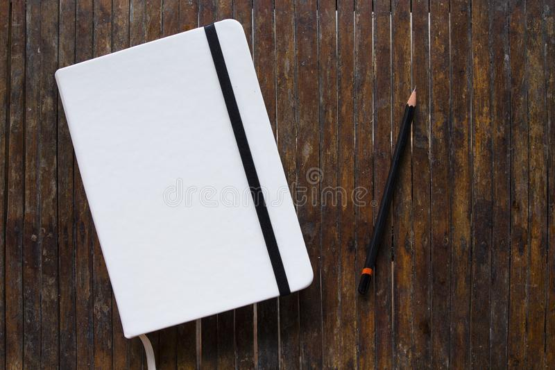 White cover notebook with black pencil on rustic wooden table flat lay photo. stock photos