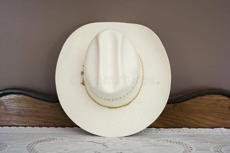 A White Cowboy Hat on an Antique Cabinet Front View stock photo