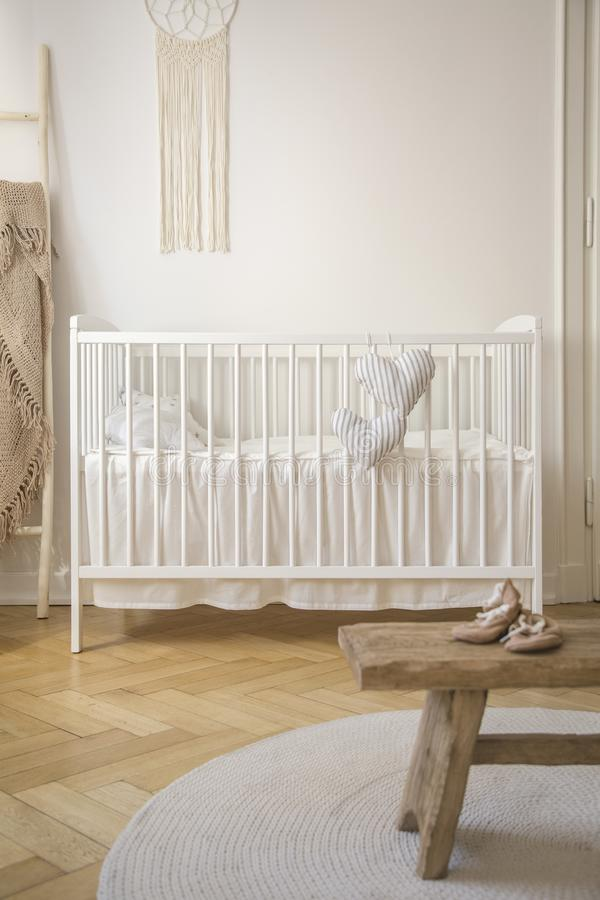 White cradle and shoes on wooden stool in baby`s bedroom interior with round rug. Real photo stock image