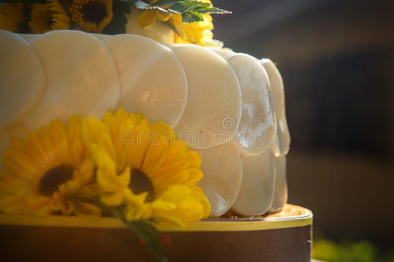 White creamy delicious cake closeup. White creamy delicious cake decorated with yellow flowers and green leafs closeup royalty free stock images