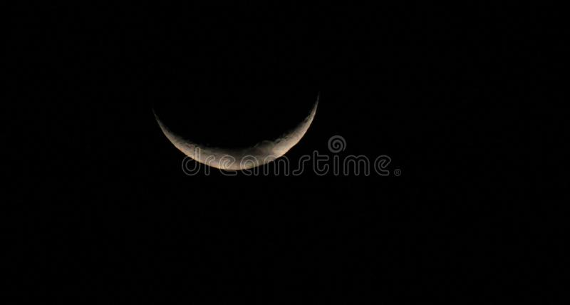 White crescent moon in a starless sky closeup. Sliver of a silver crescent moon surrounded by the dark abyss of night as seen from earth zoomed in royalty free stock photography