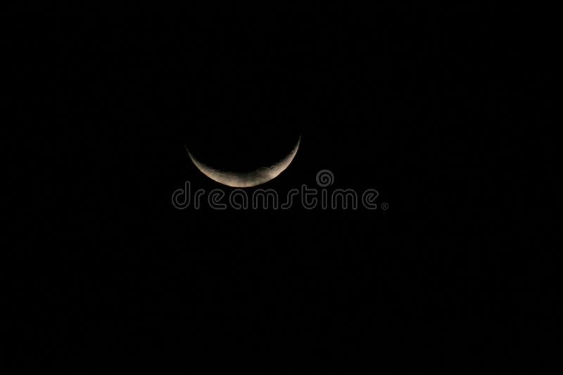 White crescent moon in a starless sky. Sliver of a silver crescent moon surrounded by the dark abyss of night as seen from earth stock images