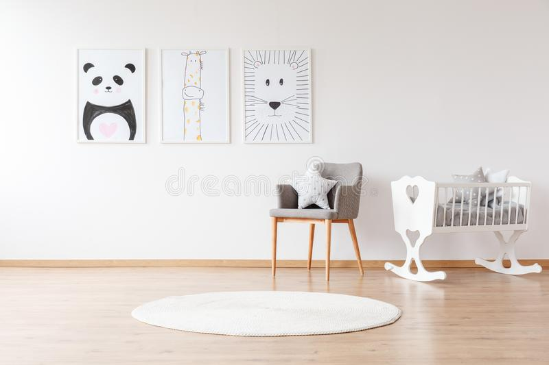 White crib in baby`s room. Grey chair with pillow and white round rug near white crib in baby`s room with animal posters on the wall royalty free stock photography