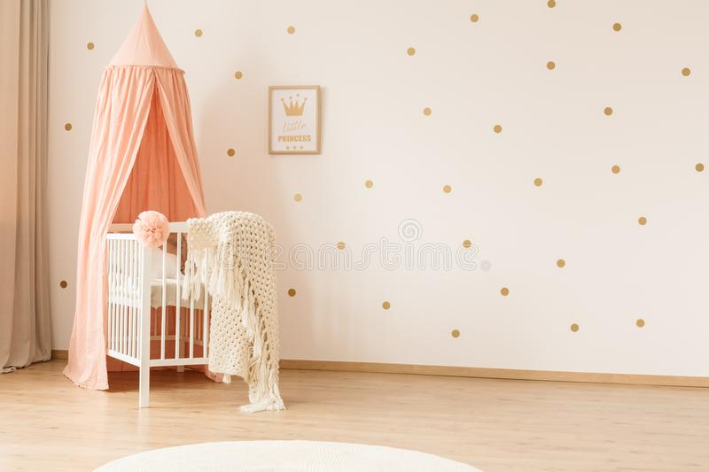White crib and copy space. Classic white crib with a peach pink canopy in a girly nursery bedroom interior with gold polka dots on the wall and copy space stock images