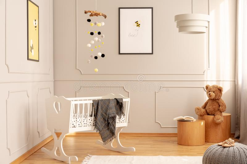 White crib in a cozy toddler room interior with bee posters, teddy bear and lamp. Real photo royalty free stock photography