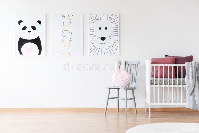 White crib in bright room. White crib and gray chair in bright room for a child with panda, giraffe and lion posters stock image