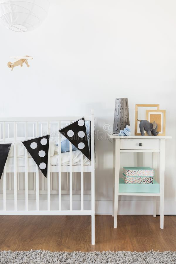 White crib and nightstand. In baby room stock photo