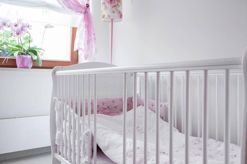 White crib in nursery room. Close-up of white crib in nursery room stock photo