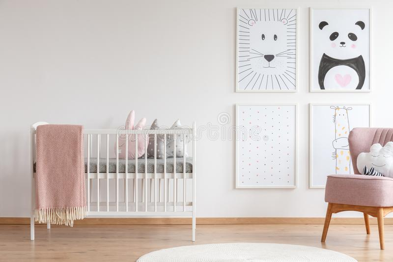 Crib in baby room. White crib with pink blanket and decorative cushions standing in cute baby room with posters stock photos