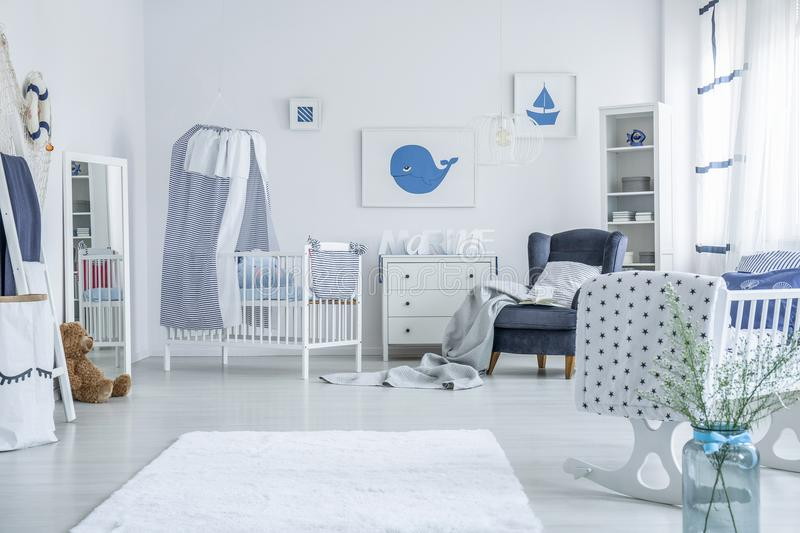 White crib with striped veil. Standing against white wall next to a chest of drawers in room for a child stock photography