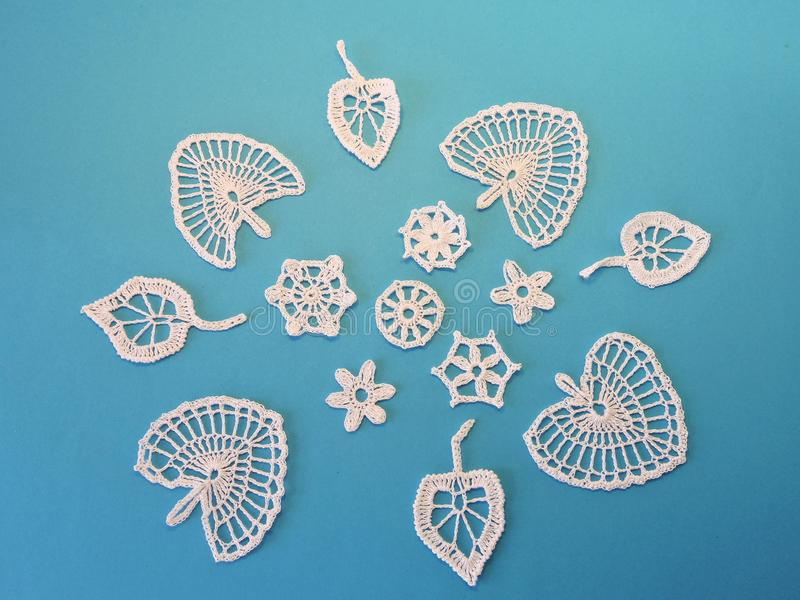 White crocheted leafs and flowers on blue background stock photo