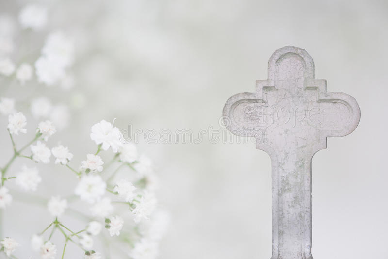 White Cross and Hope Funeral Card. White stone cross with Hope inscription engraved on it and babys breath flowers; inspirational postcard for condolences and stock photos