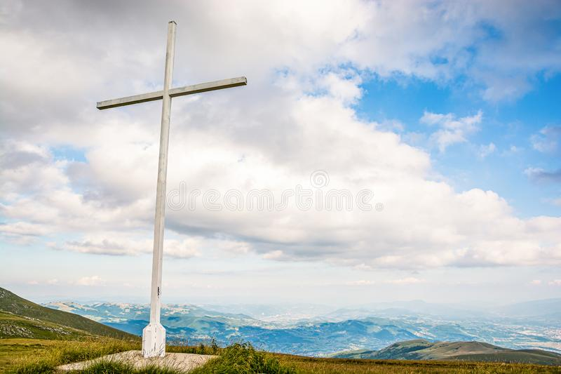 White cross on meadow in green mountainsnear Travnik city in Bosnia and Herzegovina.  royalty free stock image