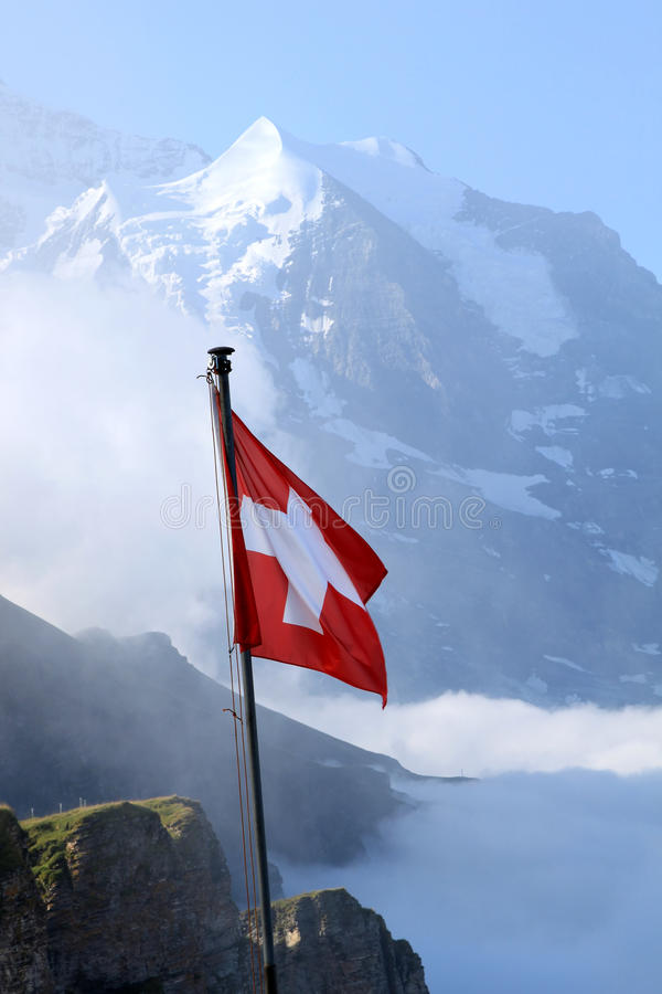 White cross of the red Swiss flag in the Alps. The red Swiss flag flies from the mountain of Mannlichen in the foggy Alps of the Bernese Oberland in Switzerland stock images