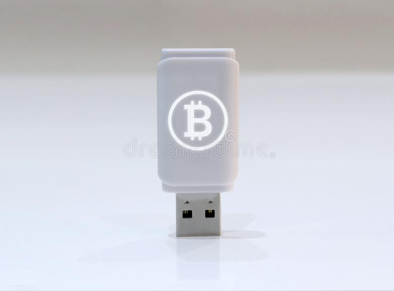 Cryptocurrency private key with glowing Bitcoin logo - USB Flash drive on white surface stock images