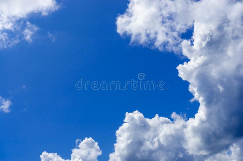 White, cumulus clouds against the blue sky. Place for text royalty free stock photo