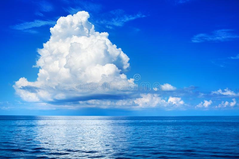 White cumulus clouds in blue sky over sea landscape, big cloud above ocean water panorama, beautiful seascape, cloudy weather royalty free stock images